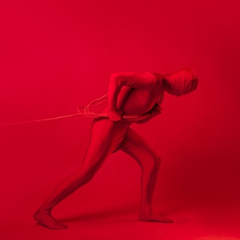 The red man drags something on a rope a concept of labor and anxiety