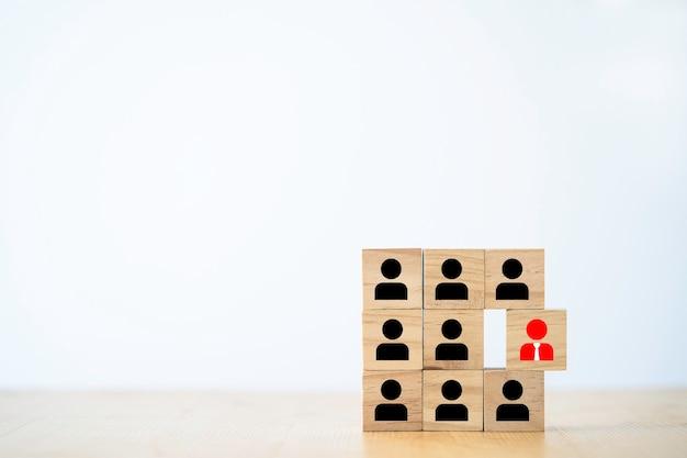 Красный значок менеджера, выдающийся из значка сотрудника, который печатает экран на деревянном блоке, разное мышление и концепцию человеческого развития.