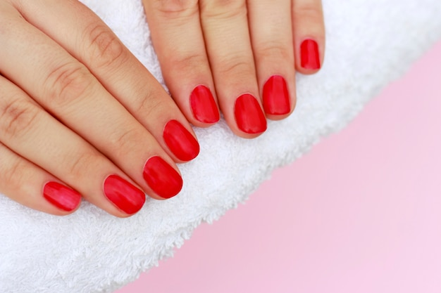 Red manicure on white towel, copy space