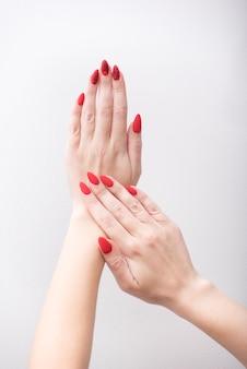 パターンを持つ赤いマニキュア。白い背景の上の女性の手