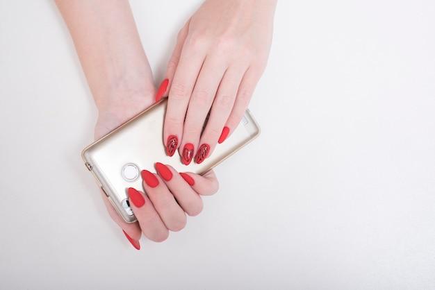パターン付きの赤いマニキュア。女性の手にスマートフォン。白色の背景