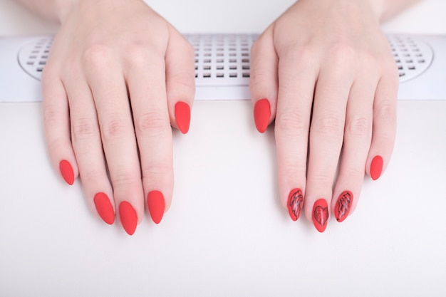 Red manicure with a pattern. female hands in manicure salon