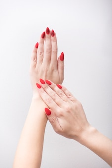 Red manicure with a pattern. female hands on a white background