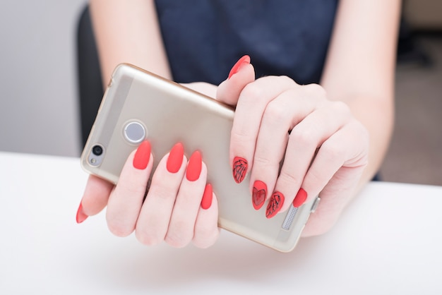 Red manicure with a pattern. smart phone in female hand.