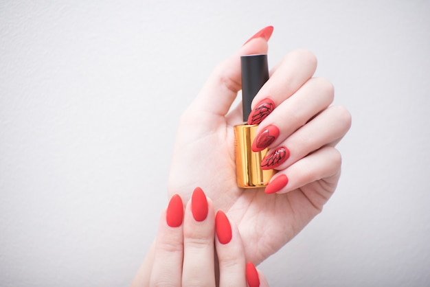 Red manicure with a pattern. vial with nail polish