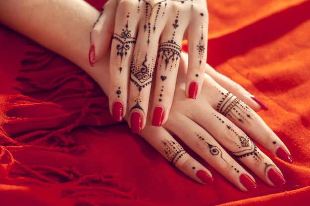 Red manicured hands with mehndi