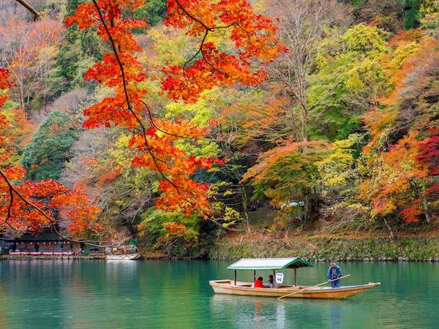 Red maple leaf and katsura river at arashiyama, kyoto.