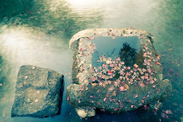 日本の禅池の石の井戸の水の上に赤いカエデの木の葉が横たわっていた