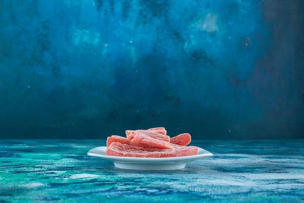 파란색 테이블에 접시에 빨간 마멀레이드.