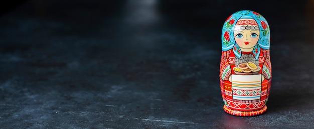 Красная матрешка. традиционный русский сувенир, символ россии. скопируйте пространство. черный бетонный фон