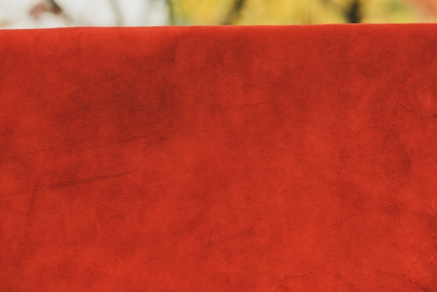 Red matte background of suede fabric. velvet texture of seamless leather. felt material.