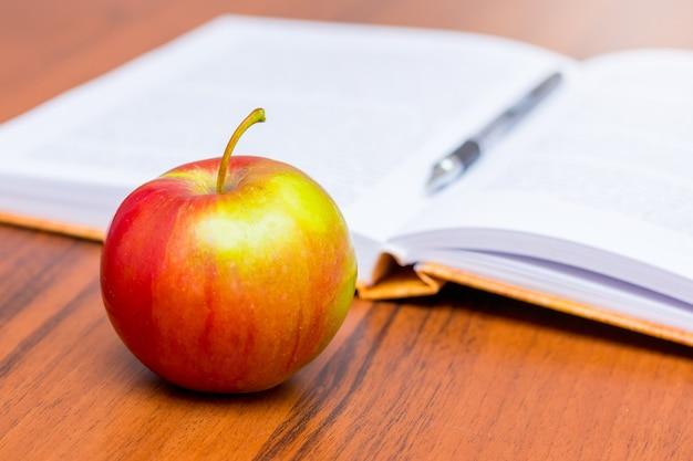 開いた本の背景に赤の成熟したジューシーなりんご