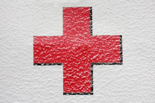 Красный медицинский крест слегка покрыт снегом на белом фоне на открытом воздухе.