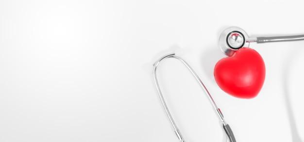 Красное медицинское сердце со стетоскопом на белой предпосылке.