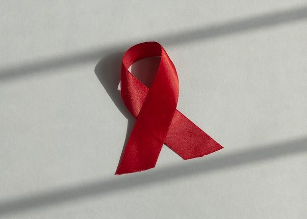 Красная медицинская лента для спида и информирования о дне вич, свернувшаяся атласным бантом