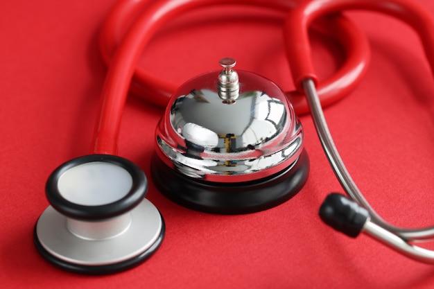 赤い医療聴診器と赤い背景の医療サービスの予定の概念の鐘