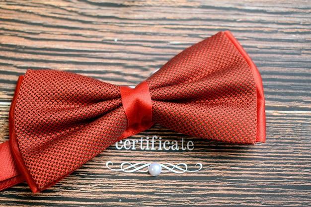 Красный мужской галстук-бабочка. деревянный фон