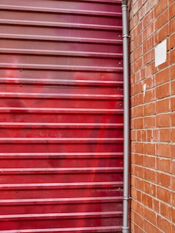 Red metal brick wall gate in city background