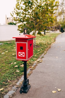 Red metal mailbox on the street. blurred background. high quality photo