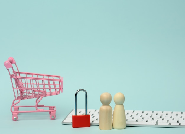 A red metal padlock stands on the keyboard and behind a miniature shopping cart, blue background. personal data protection concept, secure online shopping