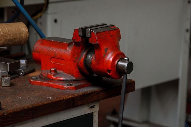 Красные металлические тиски на деревянном столе на заводе