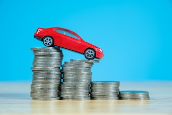 Red miniature car model on stack of coins