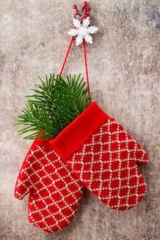 Красные перчатки рукавицы на предпосылке рождества деревянной.