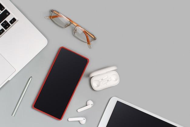 복사 공간이 있는 회색 책상 위에 있는 노트북 근처에 있는 빨간색 휴대폰, 이어폰 및 안경. 휴대 전화 모형
