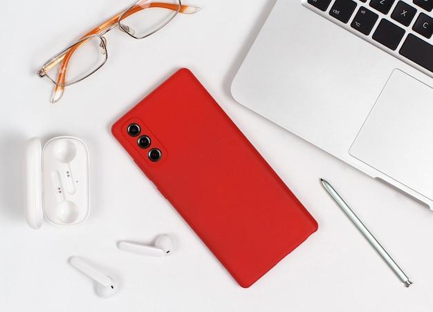 赤い携帯電話、イヤホン、白い背景の上のラップトップの近くにメガネ