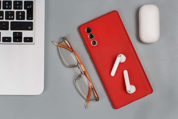 Red mobile phone, earphones and glasses near laptop on grey background