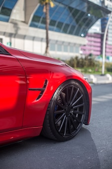 Red model sedan in the landmark parking, front wheel view