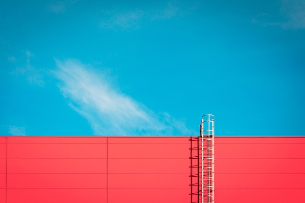 A red modern facade of an industrial building, warehouse or shopping center with a long metal staircase against the blue sky