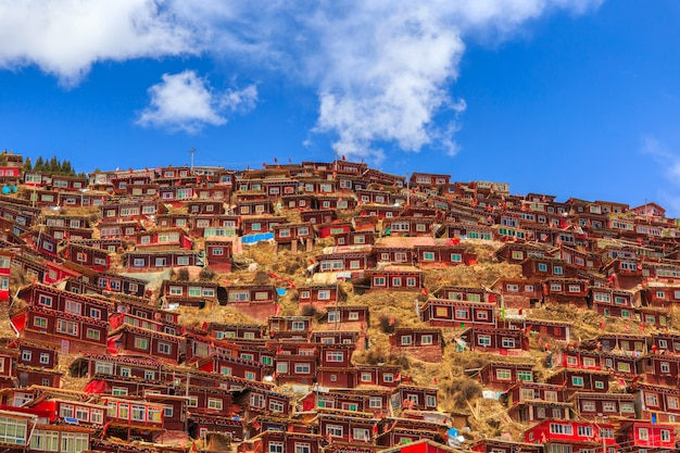 Red monastery at larung gar (buddhist academy) in sunshine day and background is blue sky, sichuan, china