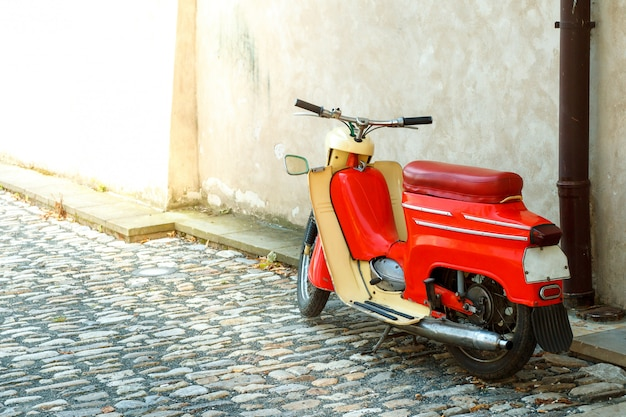A red moped stands by the wall on the pavement of the old city
