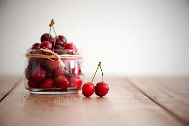 레드 모렐로 체리 - 나무 테이블에 있는 여름 딸기. 신선한 레드 하트 체리입니다. 과일과 비타민. 건강한 영양