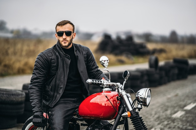 Red motorbike with rider. a man in a black leather jacket and pants stands sideways in the middle of the road. tires are laid on the background