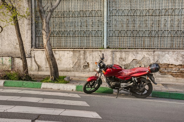Red motorcycle parked on street in front of weathered wall