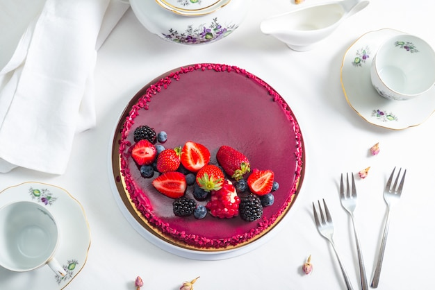 Red mousse cake with berry decor on the table with porcelain tea pot and cups