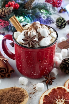 Red mug of hot chocolate with marshmallow, anise and cinnamon sprinkled with cocoa powder on a wooden table