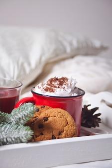 冬の早朝、ベッドの上の白いトレイにココアの赤いマグカップ
