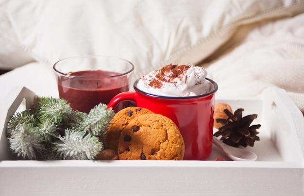 冬の早朝のベッドの上の白いトレイにココアの赤いマグカップ