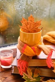 Красная кружка с шарфом и красным листом на фоне окна после дождя. согревающие осенние напитки. уютная домашняя атмосфера