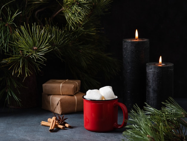 Red mug with cocoa, marshmallow and cinnamon on a dark blue background with lit candles, gifts and fir tree. dark and mood image
