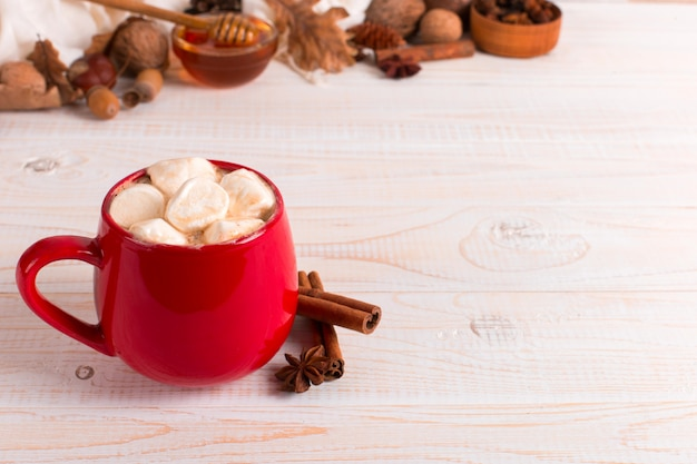 Red mug with cocoa and marshmallows, on a background of a scarf and dry leaves. autumn mood, a warming drink.
