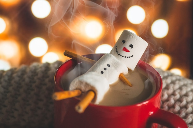 Red mug with hot chocolate with melted marshmallow snowman on bokeh background
