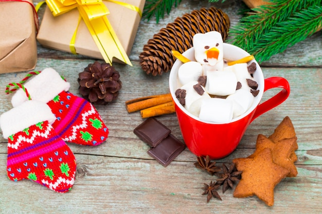 Red mug with hot chocolate with melted marshmallow snowman on wooden background with gifts and christmas decorations.