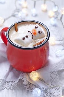 溶けたマシュマロ雪だるまとホットチョコレートの赤いマグカップ