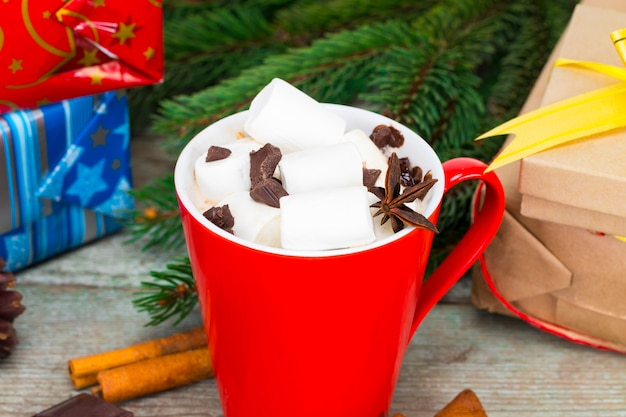 Red mug with hot chocolate with melted marshmallow on wooden background with gifts and christmas decorations