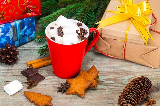 Red mug with hot chocolate with melted marshmallow on wooden background with gifts and christmas decorations.