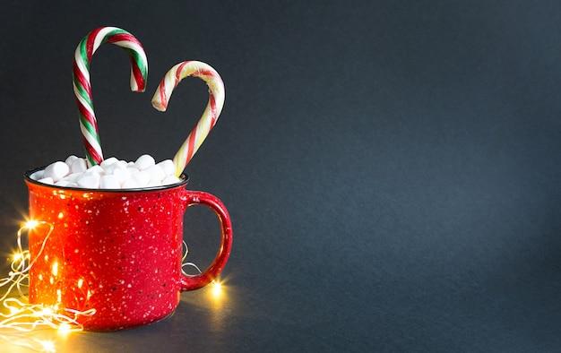 마시멜로와 카라멜 사탕 지팡이가 있는 빨간 머그는 하트 모양과 검정색 배경에 화환의 불빛입니다. 크리스마스, 새해, 축제 분위기. 복사 공간
